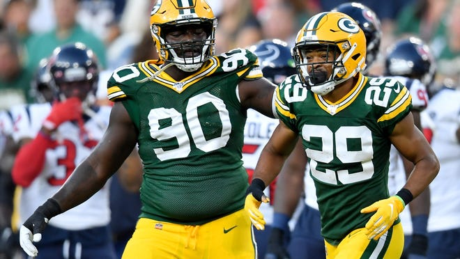 Montravius Adams, left, and Ka'dar Hollman of the Green Bay Packers celebrate after Hollman made an interception in a preseason game at Lambeau Field in August 2019.