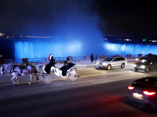 People ride on a horse-drawn carriage in traffic near the Niagara Falls illuminated by new LED lights, in Niagara, Ontario.