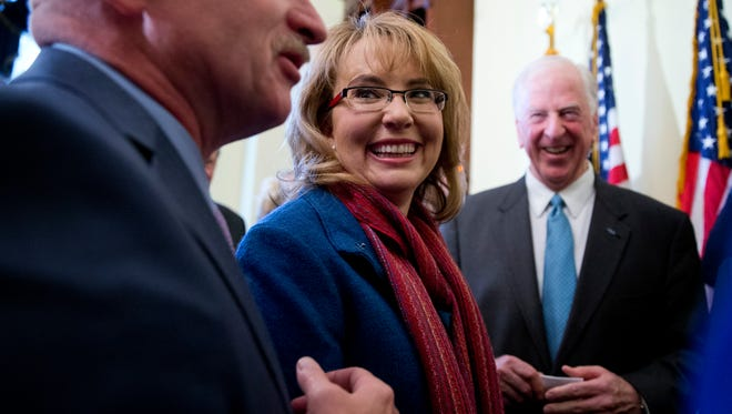 Gabby Giffords looks toward her husband, Mark Kelly, after speaking on Capitol Hill on March 4, 2015, about bipartisan legislation on gun safety.