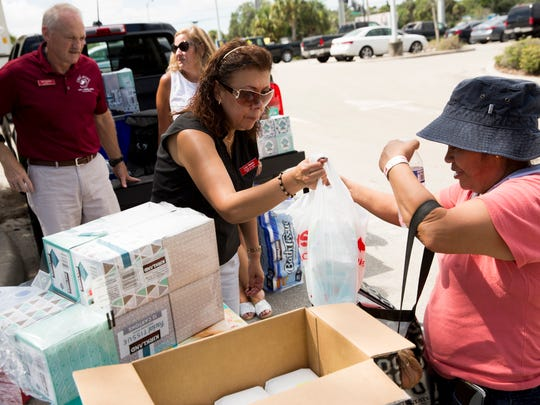 Lety Santos, an Outreach Coordinator at Cafe of Life, hands basic items such as groceries, toiletries, and diapers to Lucia Lopez, a resident on McKenna Avenue, outside the CVS Pharmacy on Bonita Beach Road and Imperial Parkway Thursday, Aug. 31, in Bonita Springs. Floodwaters, while still high as a foot in some areas, finally began to recede northeast of the Imperial Parkway and Bonita Beach Road intersection in Bonita Springs as residents started to assess the damage left behind.
