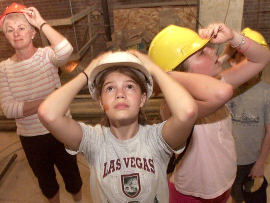 (File Photo) Kennedy Bodnarek, fifth grader at Shimek Elementary, hangs onto her hard hat as she and fifth grader Anne Staley, right, and Mary MacNeil, media specialist, check out the construction progress at the Englert Theatre, Thursday, May 6, 2004. The students helped raise $2000 when they were second and third graders and wanted check up on their investment.