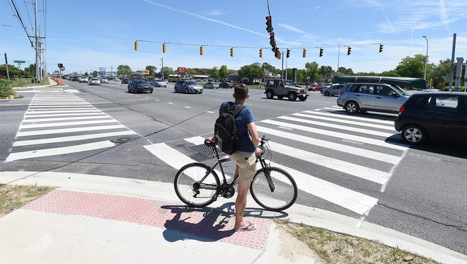 In this file photo, a bicyclist waits at the newly renovated crosswalk along Coastal Highway.