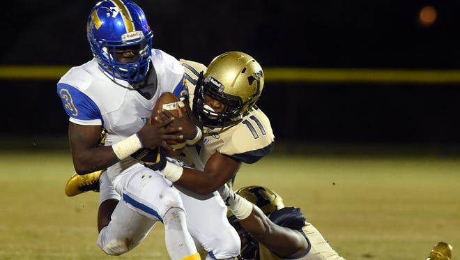 Titusville's Dontavious Marcus (3) tries to get past Treasure Coast's Eric Gaiter (11) Thursday, Nov. 3, 2016, during their high school football game at South County Regional Stadium in Port St. Lucie.