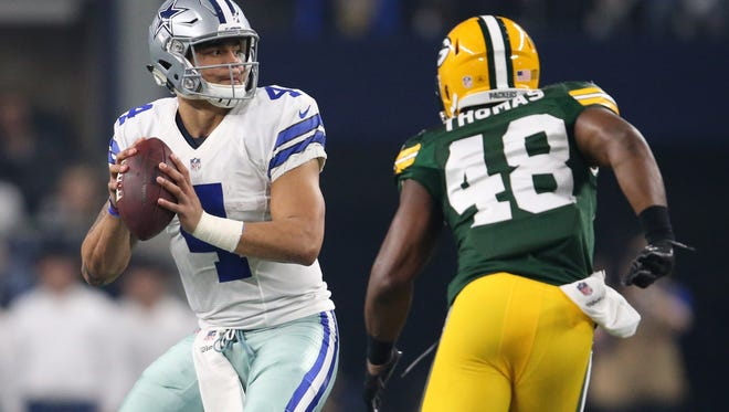 Dallas Cowboys quarterback Dak Prescott (4) drops back to pass against Green Bay Packers inside linebacker Joe Thomas (48) during the second quarter in the NFC Divisional playoff game at AT&T Stadium.