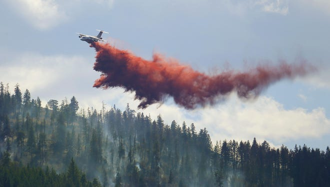 An airplane tanker drops fire retardant on a wildfire Friday north of Twisp, Wash.