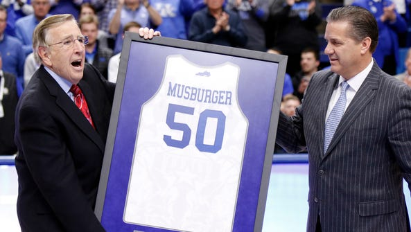 Brent Musburger, left, is presented with a framed jersey