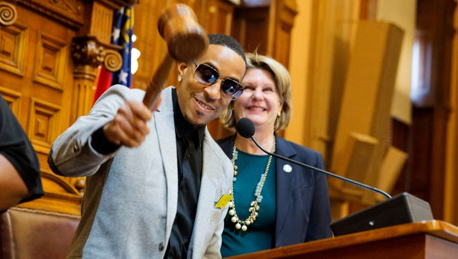 Rapper Ludacris, left, plays with the gavel as House Speaker Pro Tempore, Rep. Jan Jones, R-Milton, watches while Ludacris is recognized on the House floor at the Capitol, Thursday, March 19, 2015, in Atlanta.
