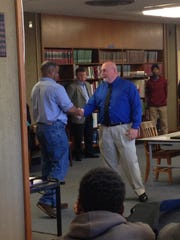 Bolton principal Clovis Christman (right) shakes hands, while introducing Teague as coach in February.