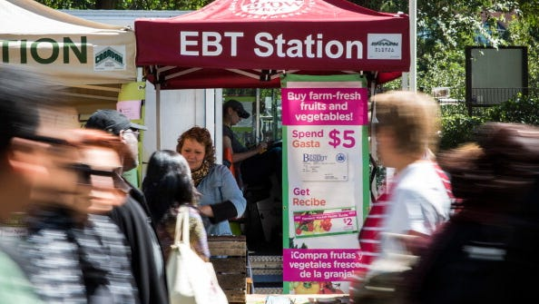 People walk past an Electronic Benefits Transfer station in the GrowNYC Greenmarket in Union Square in September 2013.