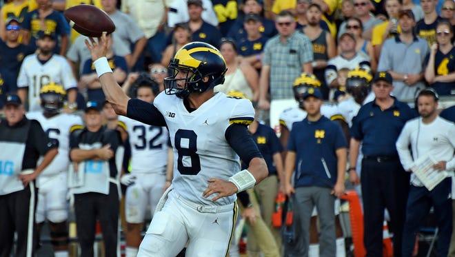 Sep 23, 2017; West Lafayette, IN, USA; Michigan quarterback John O'Korn passes while Purdue linebacker Ja'Whaun Bentley tackles him in the 2nd half at Ross-Ade Stadium.