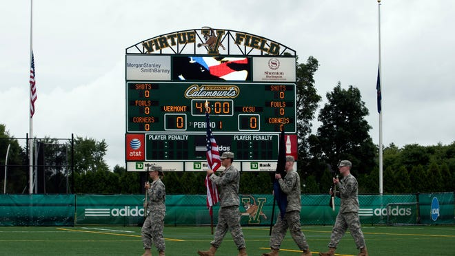 The Color Guard takes the field for the National Anthem in front of the scoreboard at Virtue Field.