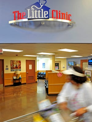 A shopper pushes a cart past the Little Clinic inside Kroger in Murfreesboro.
