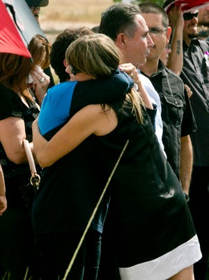 "Roxanne Warneke, right, embraces friends and family at the funeral of her husband, William ""Billy"" Warneke, who died fighting the Yarnell Hill Fire on July 10, 2013."