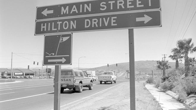 In June of 1989, Spectrum photographer Nancy Rhodes captured the then image showing the intersection of Hilton Drive, Main and Bluff streets in St. George. The Hilton Hotel on Hilton Drive has since been renamed and is currently a Crystal Inn while the creation of Black Ridge Drive has rerouted Hilton Drive and it no longer intersects with Bluff Street. The sign for the Ridgeview Inn can be seen in the now image, taken by Spectrum photographer Jud Burkett, but it no longer stands on the northwest corner of the intersection. The site is now an empty lot. On the southeast corner, the JB's Restaurant looks much the same as it did in 1989 except for the fact that it is now a Black Bear Diner. Other differences include the freeway overpass at Exit 6 in the background which has several additional lanes of travel for traffic crossing over the bridge, numerous additional communications towers atop Webb Hill and dozens of new homes have been built in Bloomington Hills beneath those towers.