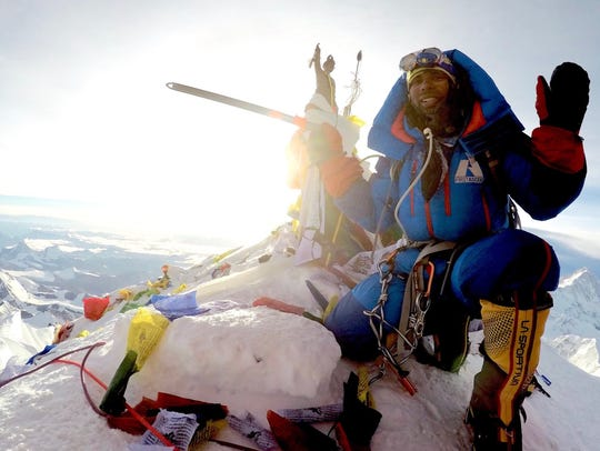 Neal Kushwaha poses at the summit of Mount Everest.