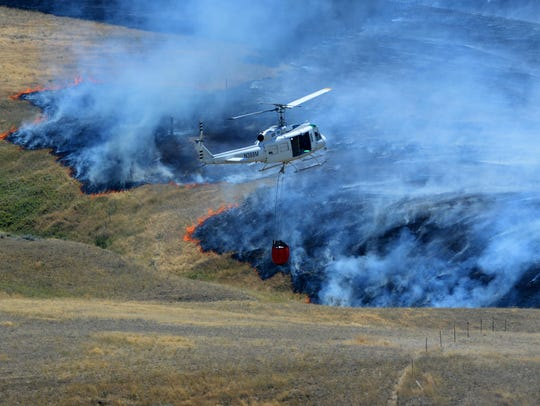 A DNRC helicopter battles a grass fire at Vinyard Road and Thunder Road on the edge of Great Falls. Several homes were threatened during the blaze.