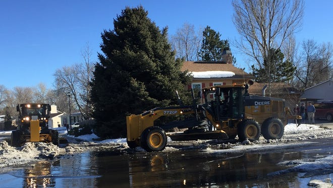 Graders from the city of Fort Collins Streets Department work Wednesday to clear ice dams at the intersection of Arctic Fox Drive and Antelope Street.