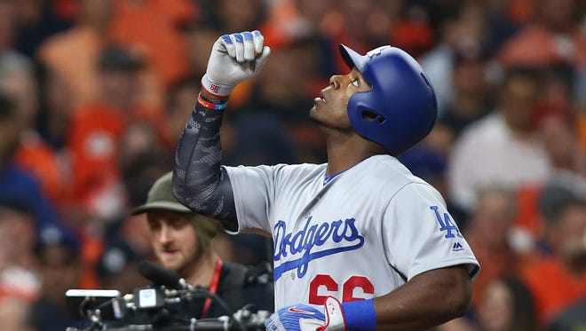 Yasiel Puig points to the sky after hitting a two-run home run in the ninth inning.