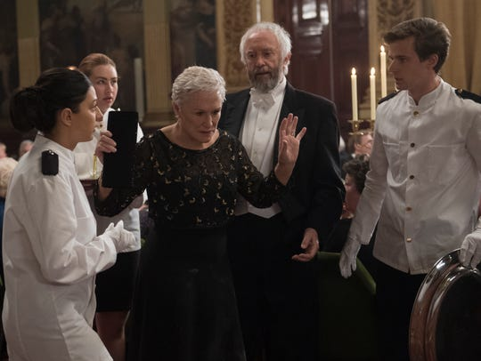 """After Joe (Jonathan Pryce, center) receives his Nobel Prize, Joan (Glenn Close) leaves the celebratory dinner in frustration in """"The Wife."""""""