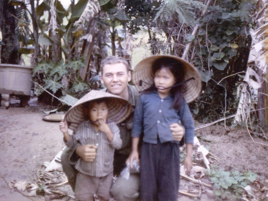 Tony Packowski with orphaned children during his first tour in the Vietnam War from August 1965 to September 1966.