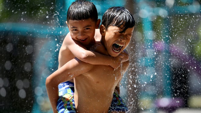 Isaiah  Rodriguez carries his cousin Bradyn Lagares through the cooling waters of the Edgerton Recreation Center Spray Park, Monday during Cool Sweep. FROM MAX: Just love the expressions of these two kids enjoying summer.