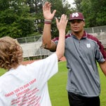 Aiden Riley gets a high five from football player Dak Prescott at the Haughton football camp Saturday morning.