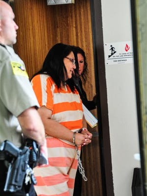 In this photo taken on Tuesday, Aug. 18, 2015, Janice Howe exits the elevator at the courthouse after a hearing, in Pierre, S.D. Howe, who lived for more than a decade with an outstanding arrest warrant, has pleaded guilty to a felony for violating election law.  (Phu Nguyen /Capital Journal via AP) MANDATORY CREDIT