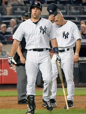 New York Yankees' Mark Teixeira reacts after fouling a ball off his leg as manager Joe Girardi, right, reacts during the sixth inning of a baseball game against the Minnesota Twins Monday, Aug 17, 2015, at Yankee Stadium in New York. Teixeira had to leave the game. (AP Photo/Bill Kostroun)