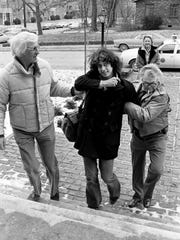 "Arlo Guthrie, center, got a Nashville welcome on March 3, 1978, that was worthy of a scene from ""Alice's Restaurant."" After being apprehended by sheriff's deputies Tommy Kerkeles, left, and Wayde Ray at Nashville Municipal Airport, Guthrie and friend Mae Axton, back, are being rush into Elliston Hall on Louise Avenue for a television interview that he was late to because his plane had been delayed. Guthrie is in town for his first concert at the Grand Ole Opry House."