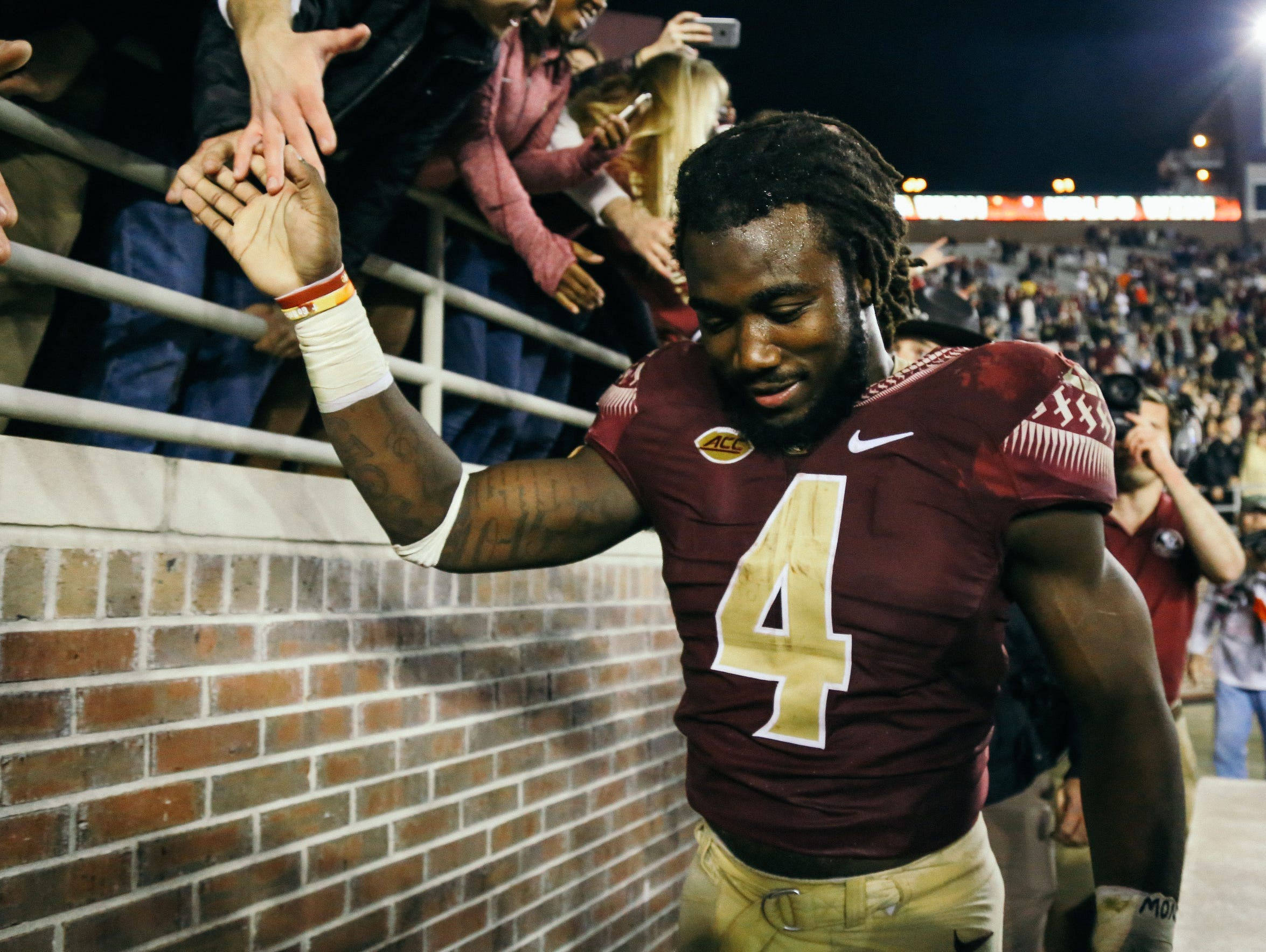 Dalvin Cook (4) celebrates with fans after beating