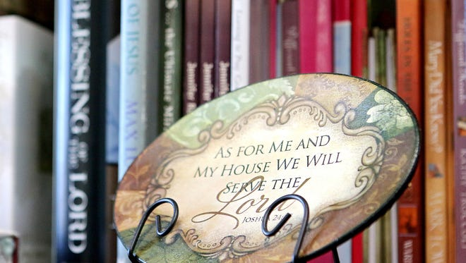 A decorative piece with scripture sits on a book shelf filled with Christian-based literature in Julie's office, where she helps others in situations she once was in seek recovery.