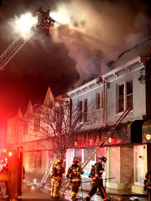 Firefighters battle a blaze in Lockland late Saturday. No one was injured, but the buildings suffered serious damage.