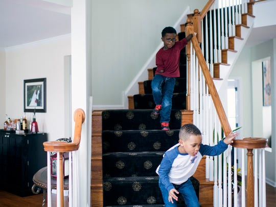 Chase Merriweather, 5, top, guides himself downstairs