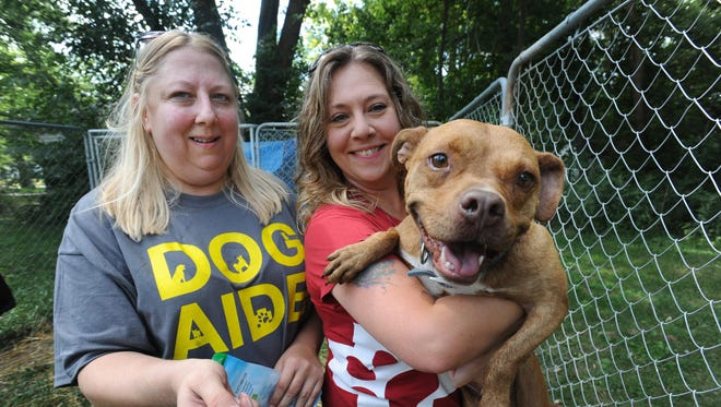 Dog Aide volunteer Dawn Lamsa, left, and executive director Jen Clarkson bring treats and a toy to Coco, a pit bull living in the Brightmoor section of Detroit.