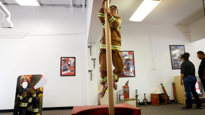 Taylor Gaytan slides down a pole Thursday during an open house event at the new Bloomfield fire administration building.