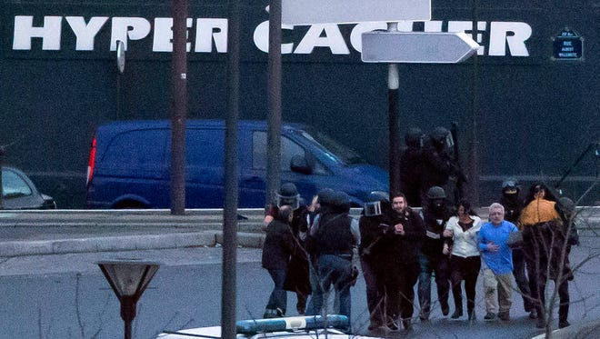 Security officers escort released hostages after they stormed a kosher market to end a hostage situation, Paris, Friday, Jan. 9, 2015. Explosions and gunshots were heard as police forces stormed a kosher grocery in Paris where a gunman was holding at least five people hostage.