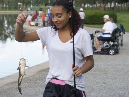 Tia Robinson, age 15, of York carries her fish to the judging table during Labor Day fishing derby at Kiwanis Lake in York Monday September 1, 2014. Paul Kuehnel - Daily Record/Sunday News   Paul Kuehnel