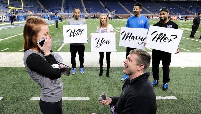 Golden Tate, right, watches as Eric Gestring pops the big question to girlfriend Darien Holden.