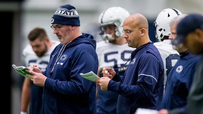 Penn State offensive coordinator Joe Moorhead, front left, and coach James Franklin check notes during NCAA college football practice Wednesday, Nov. 15, 2017, in State College, Pa. (Joe Hermitt/PennLive.com via AP)