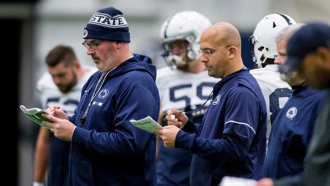 Penn State offensive coordinator Joe Moorhead, front left, and coach James Franklin check notes during NCAA college football practice Wednesday, Nov. 15, 2017, in State College, Pa. Moorhead was hired this week as Mississippi State's head coach.