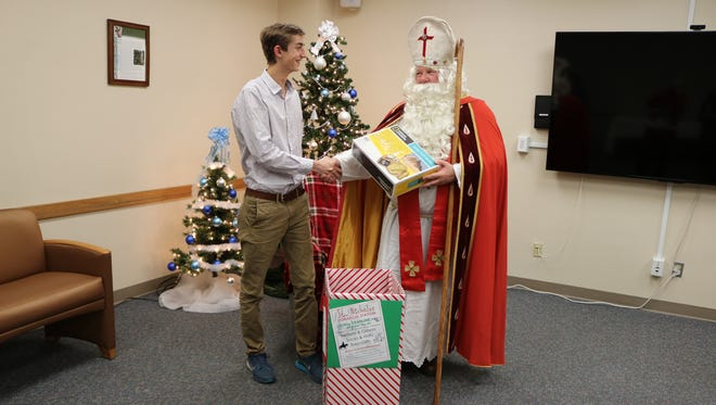 """Aidan Shank, 16, of Sheboygan, greets St. Nick at the annual """"Visit with St. Nicholas"""" event at St. Nicholas Hospital on Dec. 5 after sharing his donation."""
