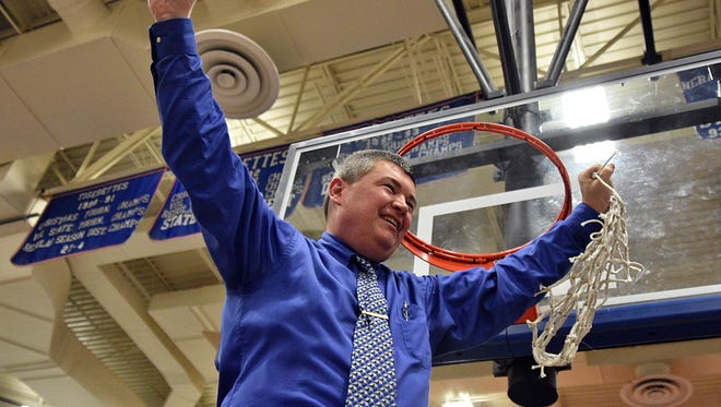 Macon County head coach Jason Welch cuts down the net following the Tigers' 69-58 victory over Tyner Academy in Monday's Class AA sectional.