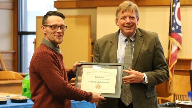 Judge Bruce Winters, right, presents Jeffery Schill, left, with his certificate after graduating from Ottawa County's Drug Court program.