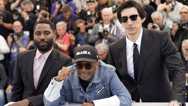 "Director Spike Lee, center, poses with his ""BlacKkKlansman"" stars John David Washington, left, and Adam Driver in Cannes."