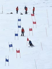 A coach follows a young racer down a slalom course at Squaw Valley Ski Area near Truckee, Calif. on Jan. 16, 2015.
