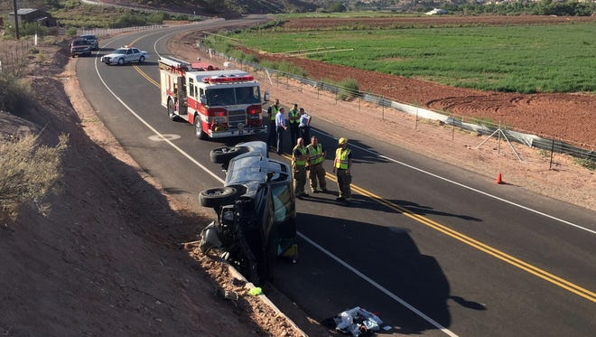 St. George Police Department officers investigate the scene of the accident while St. George Fire Department firefighters wait for a tow truck to help them clear the pickup truck from the roadway after a Dodge pickup truck struck a concrete barrier while negotiating a curve on Indian Hills Drive Monday, Aug. 17, 2015.