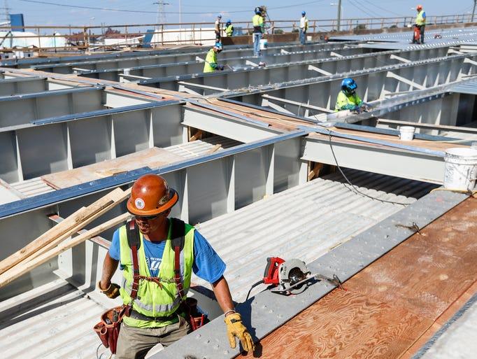 Workers prepare the steel girders before installing