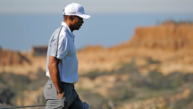 Tiger Woods walks up the 13th during the first round of the Farmers Insurance Open golf tournament at Torrey Pines Municipal Golf Course.