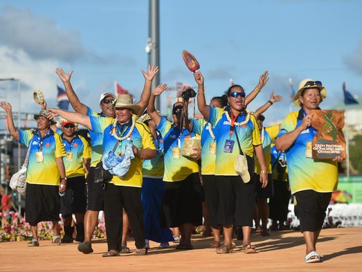Tokelau delegates wave towards the crowd as they make