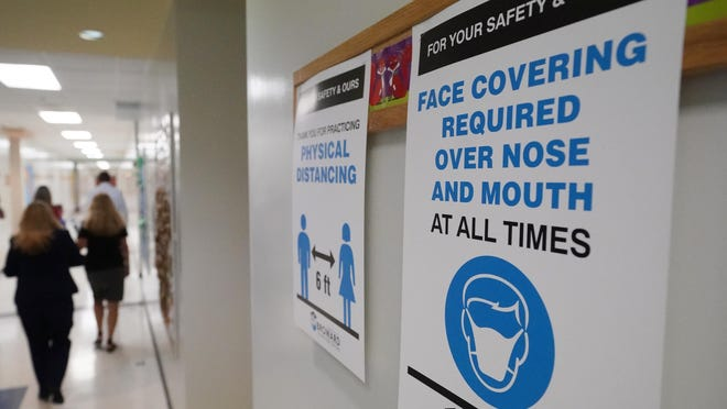 Signs in a hallway remind students to wear masks and distance themselves at Fox Trail Elementary School in Davie, Florida.
